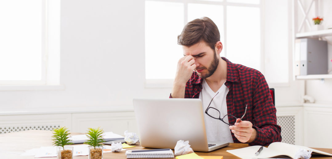 Eyes pain. Tired, overworking businessman with laptop in modern white office interior. Handsome man in casual at work with computer, job problems concept.