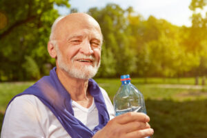 Starszy uśmiechnięty mężczyzna trzymający butelkę z wodą.